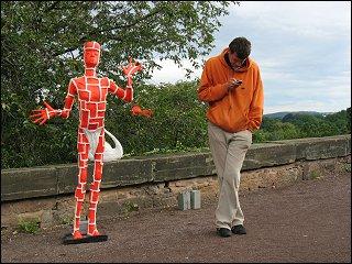 Skulptur und telefonierender Passant auf einem Kassler Künstlermarkt