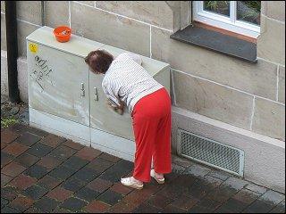 Nachbarin beim Säubern eines Schaltkastens