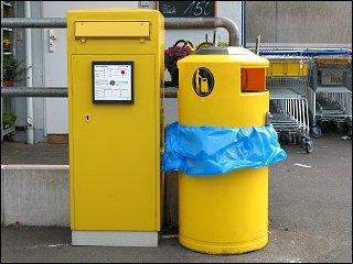 Briefkasten und Mülleimer vor einem Supermarkt