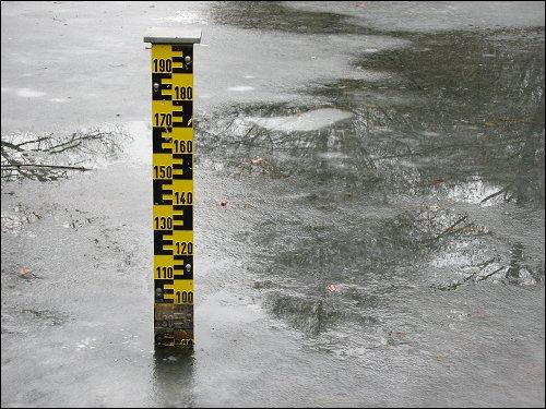Pegelstab in zugefrorenem Kanal beim Lexikaliker um die Ecke