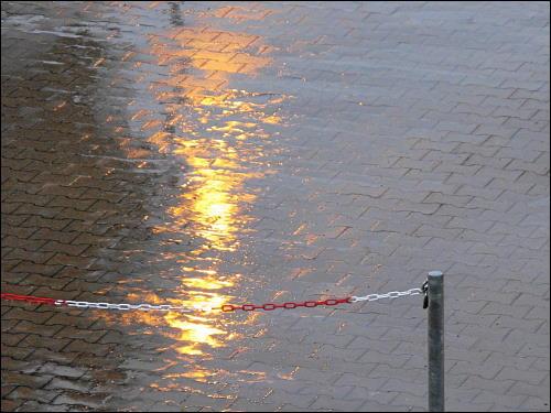 Spiegelung von Lampenlicht auf regennassem Parkplatz