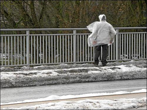 Passant mit Regenschutzfolie im Fürther Winterwind