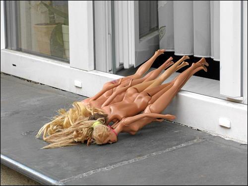 vier lufttrocknende Barbies auf einer Fensterbank in der Nachbarschaft