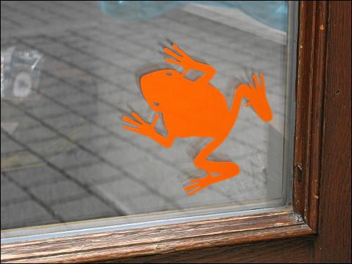 Frosch-Aufkleber an einer Ladentür in der Ludwig-Erhard-Straße