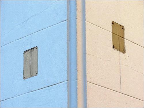 Hausecke mit entschwundenen Hinweisschildern auf Gas- und/oder Wasser-Versorgung