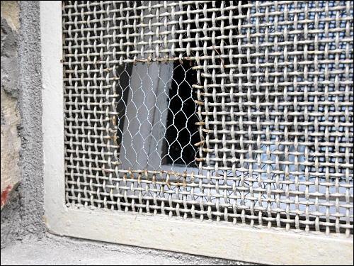 ausgebessertes Loch in einem Fenstergitter