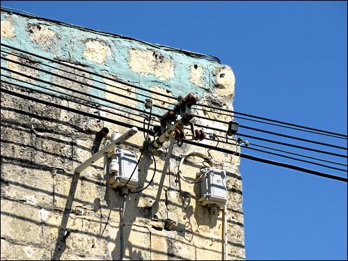 Stromleitungen und Anzapfungen an einer Hausecke