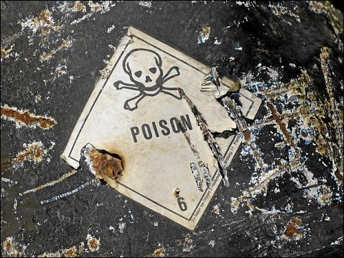 Warn-Aufkleber auf einer wild entsorgten Chemikalien-Tonne