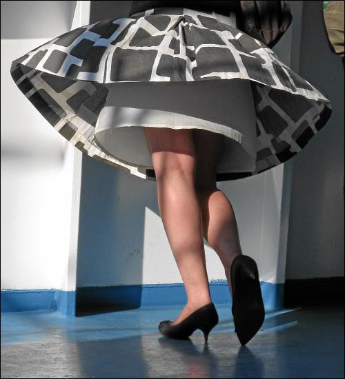 von böigen Winden dezent freigelegte Damenbeine auf einem Fährschiff