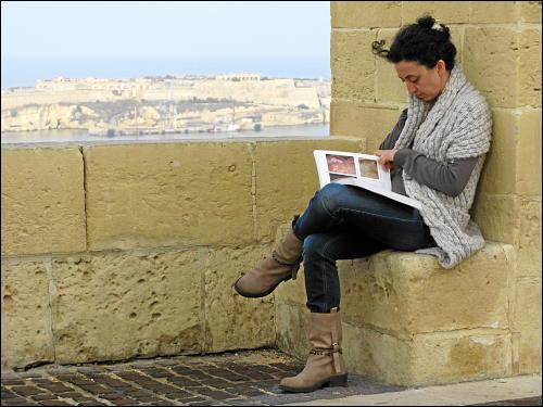 ins Lesen vertiefte Besucherin der Upper Barrakka Gardens