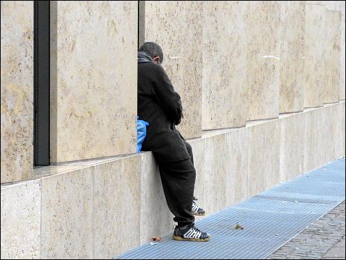 Mann, in Gebäudenische sitzend