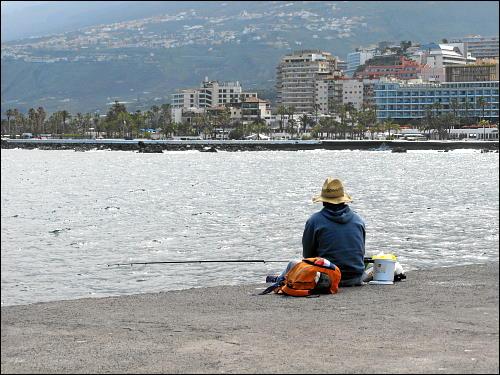 Mann mit Hut, sitzend und angelnd
