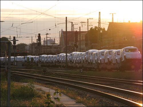 Güterzug voller Neuwagen mit weißen Schutzhauben