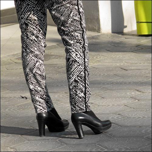 Monochrome Damenbeine auf traditionellem Pflaster in Barcelona
