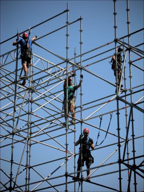 Schwindelfreie Arbeiter beim Errichten eines Baugerüstes im Castello di Udine