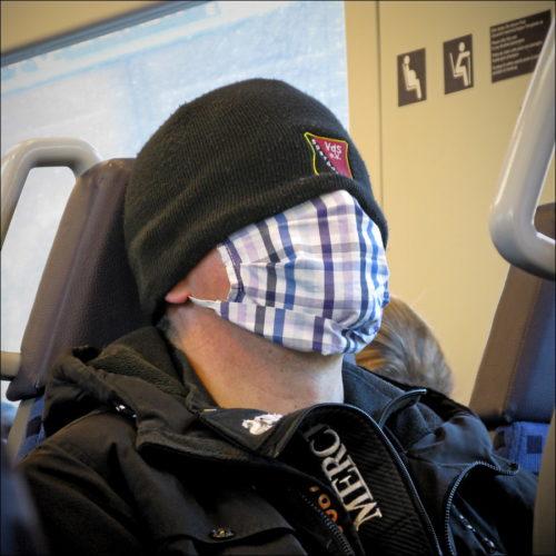 Masken-Mann im Morgenzug