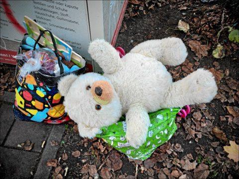 Hilfeheischender Teddy am überfüllten Altkleider-Container