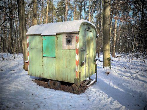 Buntes Bauwägelchen im winterlichen Wald